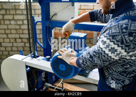 Closeup of unrecognizable young man working at modern factory repairing machine units in industrial workshop, copy - Stock Photo