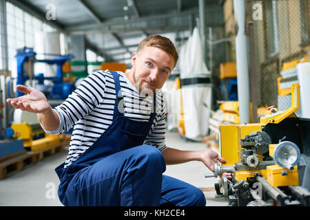 Portrait of confused repairman looking at camera in surprise while trying to fix machine units at factory - Stock Photo
