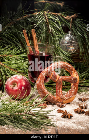 A glass of mulled wine, an apple and pretzel on a table near the Christmas tree in a house - Stock Photo