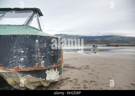Rusty old black and green fishing boat on sandy beach in Barmouth, Abermaw, Wales - Stock Photo
