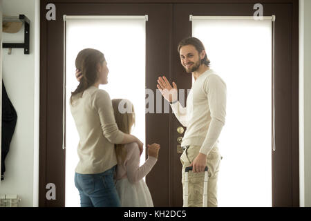 Mother and daughter seeing off father leaving for business trip, mom with kid girl saying goodbye to dad waving - Stock Photo