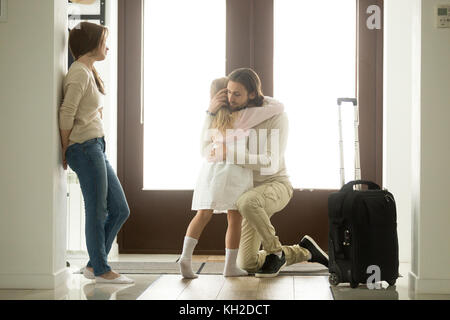 Sad father hugging little daughter before leaving for long business trip, upset dad embracing crying girl saying - Stock Photo