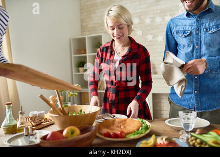 Portrait of modern young couple  standing at festive dinner table  preparing food and smiling, focus on happy blonde - Stock Photo