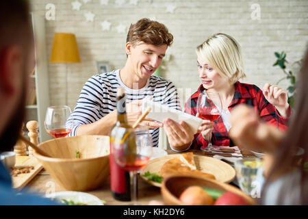 Portrait of young man and woman looking at digital tablet discussing photos while having dinner with friends sitting - Stock Photo