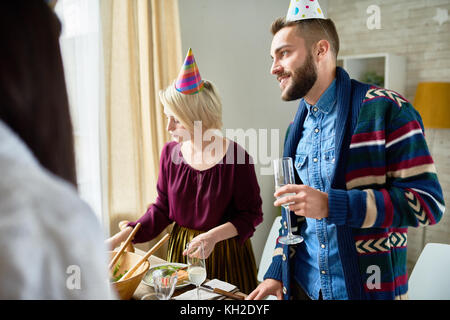 Group of happy young people wearing holiday caps celebrating Birthday with friends holding champagne glasses during - Stock Photo
