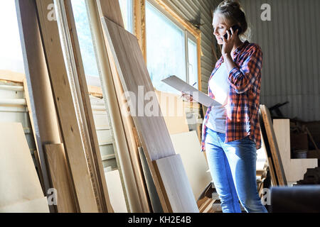 Portrait of young woman speaking by phone and holding clipboard choosing best materials from storage house, copy - Stock Photo