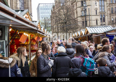 Manchester Christmas Market in Albert Square Manchester UK.  Crowds of people Christmas shopping down the tighlty - Stock Photo