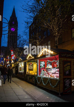 Christmas Market Stalls at the top of Brazennose street, Manchester, UK and town hall clock in the background - Stock Photo