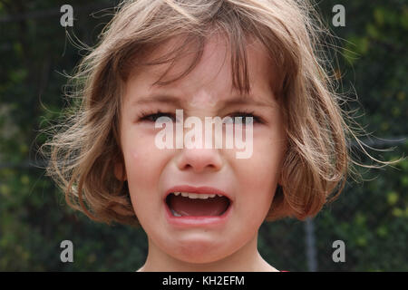 Portrait of a young girl who is very angry and upset - Stock Photo