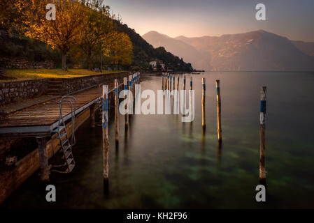 Little harbour on Iseo Lake with mountains in background, Italy - Stock Photo