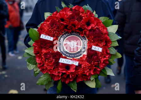 London, UK.  12 November 2017.  A member of the Football Lads Alliance carries a wreath from Arsenal supporters - Stock Photo