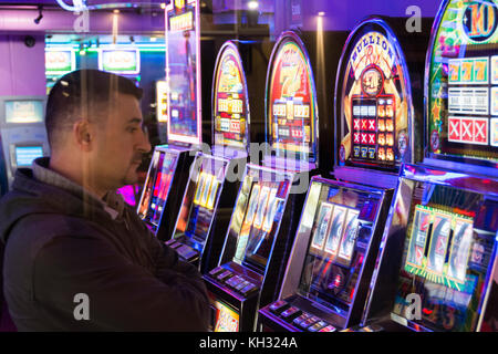 A man plays the slot machines in an amusement arcade in Chinatown in London's West End, UK - Stock Photo
