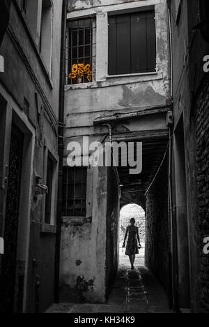 Girl walking though alley in Venice with some sunflowers in a upstairs window. Depicting Travel and discovering - Stock Photo