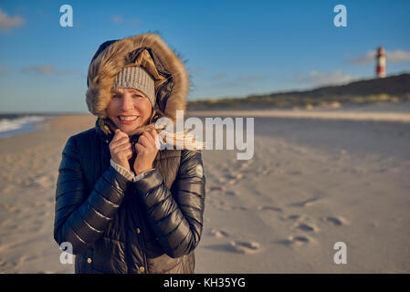 Portrait of a beautiful woman smiling while wearing a black waterproof hooded winter coat on an empty beach with - Stock Photo