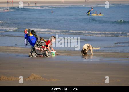 Enjoying good summer sunny weather girl playing with her dog on the Keel beach on Achill Island, Countu Mayo, Ireland - Stock Photo