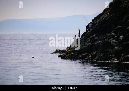 Men angling from the rocks at the feet of Moyteoge Head sea cliff at Keem Bay, Achill Island, County Mayo, Ireland - Stock Photo