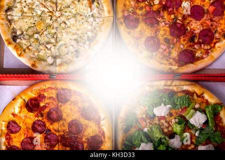 Four different pizza in boxes - Caesar, with salami and chicken with copy space. Top view - Stock Photo