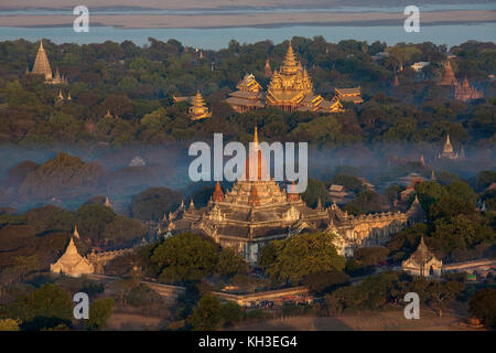 Aerial view of the early morning sunshine on the Ananda Buddhist Temple (foreground) in the ancient city of Bagan - Stock Photo