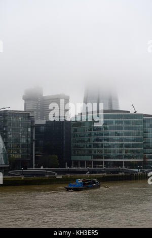The Shard shrouded in mist and cloud. Low cloud misty morning in London and River Thames. - Stock Photo