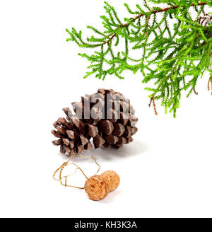 Branch of decorative home Christmas-tree, big pine cone and champagne wine cork with muselet. After New Year celebration. - Stock Photo
