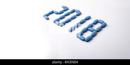 Creative 2018 new year concept made out blue medical tablets over a white background. - Stock Photo