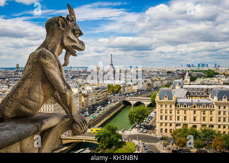 Gargoyle on Notre Dame with skyline of Paris and Eiffel tower, France - Stock Photo