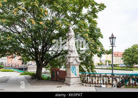 WROCLAW, POLAND - SEPTEMBER 12, 2017: old statue on waterfront near Tumski Bridge (Most Tumski, Lovers Bridge, Cathedral - Stock Photo