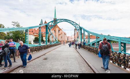 WROCLAW, POLAND - SEPTEMBER 12, 2017: tourists on pedestrian Tumski Bridge (Most Tumski, Lovers Bridge, Cathedral - Stock Photo