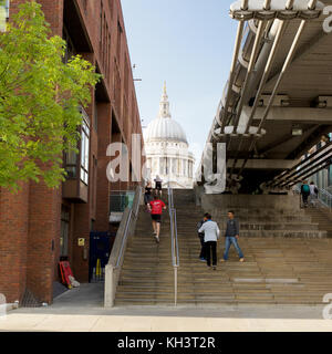 People jogging up and down steps next to The Millennium Bridge with St Pauls Cathedral in the background. London - Stock Photo