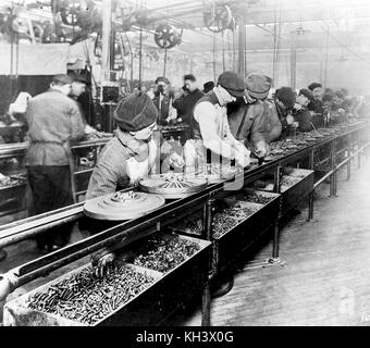 Workers on the first moving assembly line put together magnetos and flywheels for Ford autos, Ford assembly line - Stock Photo