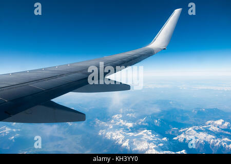 Wing of plane flying over clouds and mountains. - Stock Photo