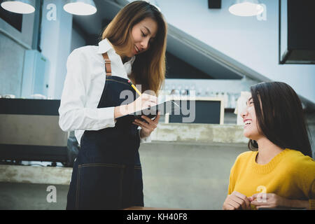 Young asian barista taking order of woman in the cafe. Cafe restaurant service, Small business owner, food and drink - Stock Photo