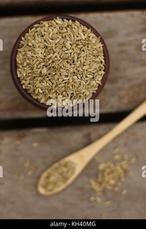 Wooden bowl filled with fennel seeds and a wooden spoon with fennel seeds over a wooden deck - Stock Photo