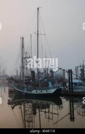 Fishing boats and pleasure craft in Steveston on a foggy morning in Richmond, British Columbia - Stock Photo