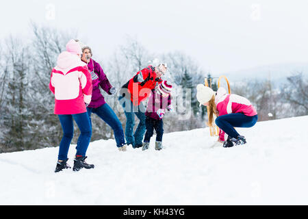 Family with kids having snowball fight in winter - Stock Photo