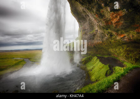 View of the Seljalandafoss Waterfall Behind from a Cave, Iceland - Stock Photo