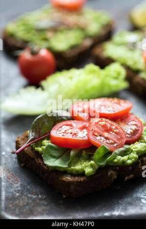 Toast with avocado, spinach and cherry tomato on whole grain rye bread. Closeup view, selective focus - Stock Photo