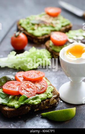 Avocado toast with spinach, tomato and boiled egg. Healthy green veggie open sandwich. Selective focus - Stock Photo