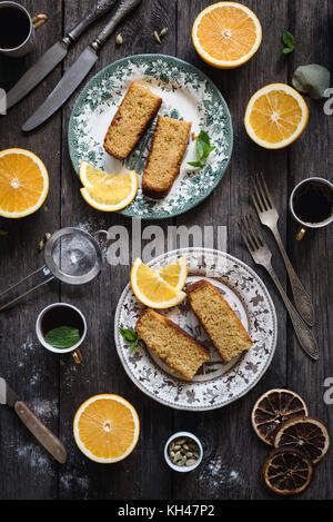 Orange cake served on vintage plate on rustic wooden table background. Food still life. Top view, vertical composition - Stock Photo