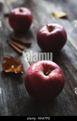 Red apples and cinnamon sticks on wooden background. Autumn food still life - Stock Photo