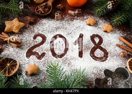 New Year 2018 written on flour and Christmas Decorations Gingerbread cookies, cinnamin, oranges, spices, nuts and - Stock Photo
