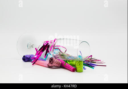 The morning after-champagne flute tipped over and covered with colorful New Years Eve noisemakers isolated on a - Stock Photo