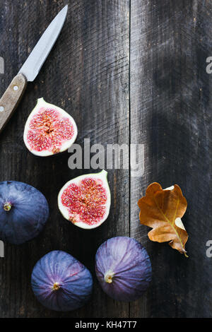 Fresh purple figs and table knife on old wooden background with copy space for text. Top view - Stock Photo