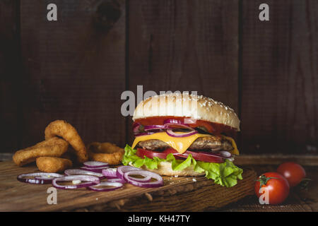 Cheeseburger and onion rings on wooden cutting board over wooden background. Closeup view with copy space for text - Stock Photo