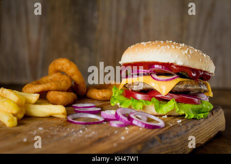 Cheeseburger, french fries and onion rings on wooden chopping board over wooden backdrop. Horizontal, closeup view - Stock Photo
