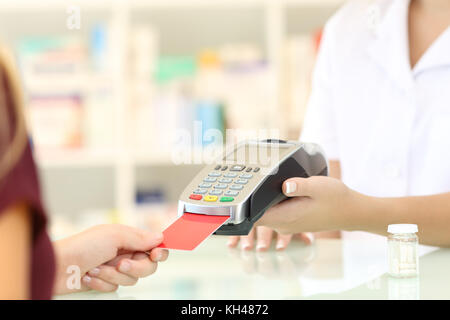 Close up of a pharmacist hands charging with credit card reader on a counter in a pharmacy - Stock Photo