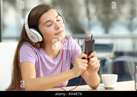 Portrait of a relaxed teen listening to music in a bar in the evening - Stock Photo