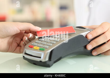 Close up of a woman hand paying with a contact less credit card in a shop counter - Stock Photo