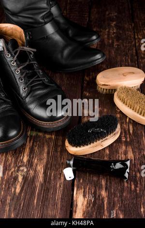Black boots on wooden background with polishing equipment, brush and polish cream - Stock Photo