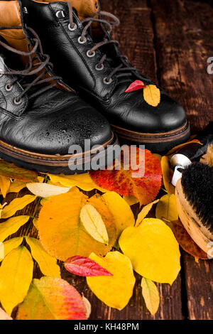 Waterproof  Black boots on wooden background with autumn leaves polishing equipment, brush and polish cream - Stock Photo